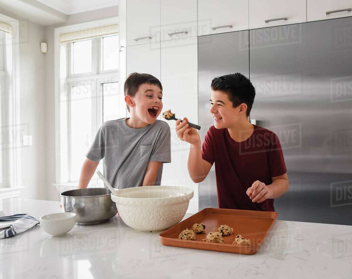 Older boy feeding cookie dough to young boy in modern kitchen Royalty-free stock photo