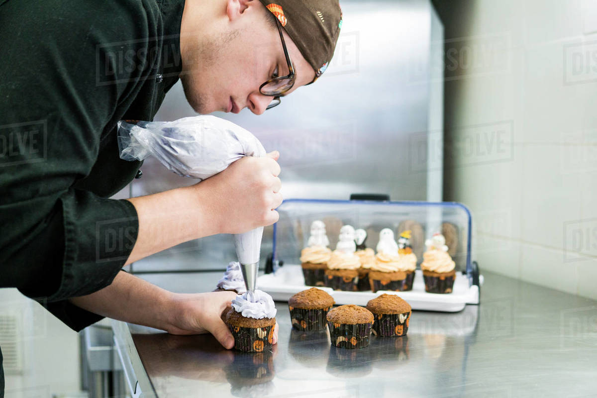 Young pastry chef is putting butter cream on cupcakes with sac a poche Royalty-free stock photo