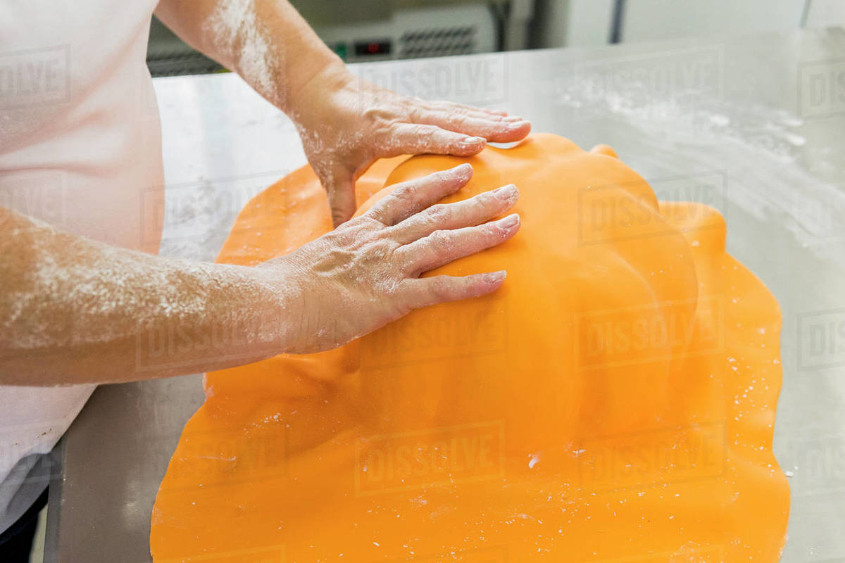 Pastry chef is molding the sugar paste for a cake with a pumpkin shape Royalty-free stock photo