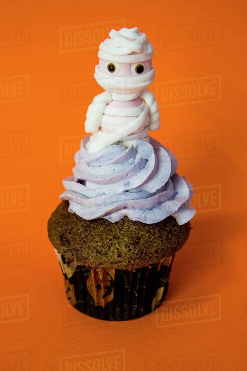 Blueberry butter cream funny mummy cupcake with orange background Royalty-free stock photo