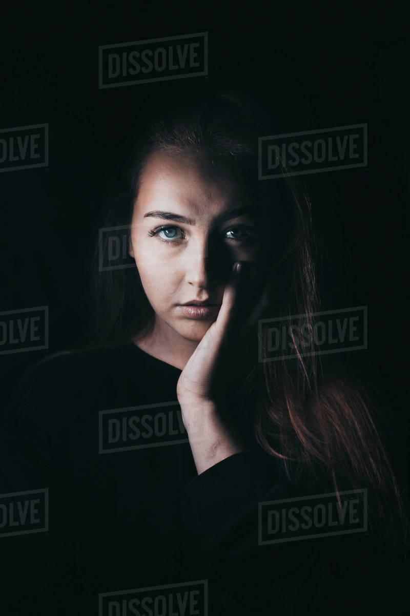 Dark haired girl looking at the camera in dark studio Royalty-free stock photo