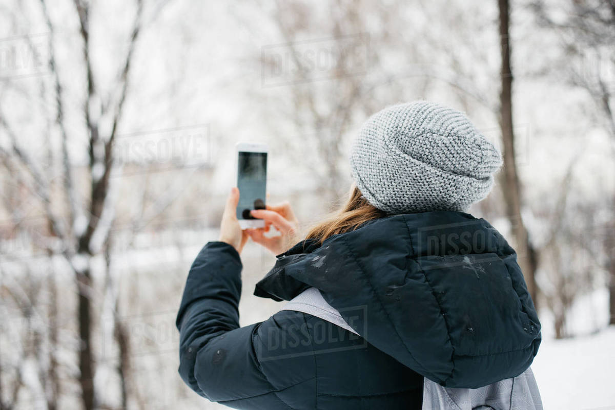 Woman taking a photo of snowy trees using a smartphone Royalty-free stock photo