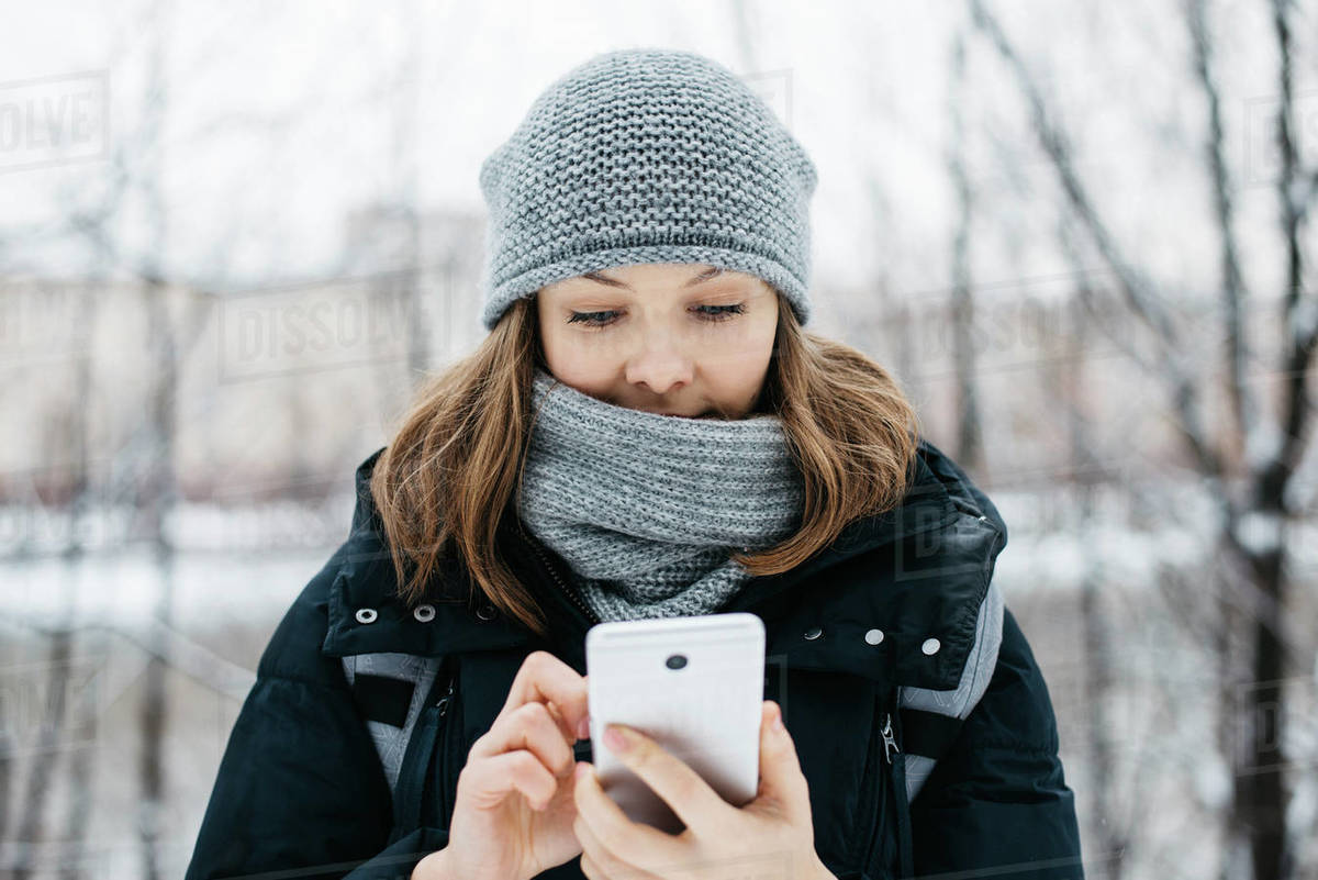 Young woman in grey hat with phone texting outdoors in winter park Royalty-free stock photo