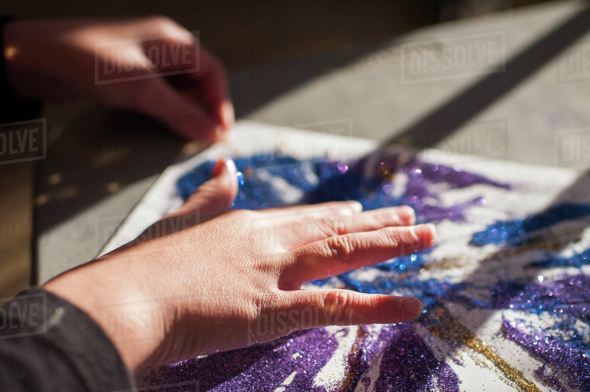 Close up of girls hands creating glitter art Royalty-free stock photo