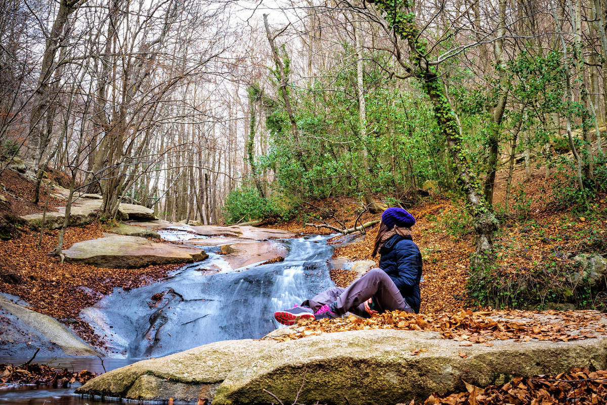 Woman sitting in the shore of the river admiring waterfall in the forest Royalty-free stock photo