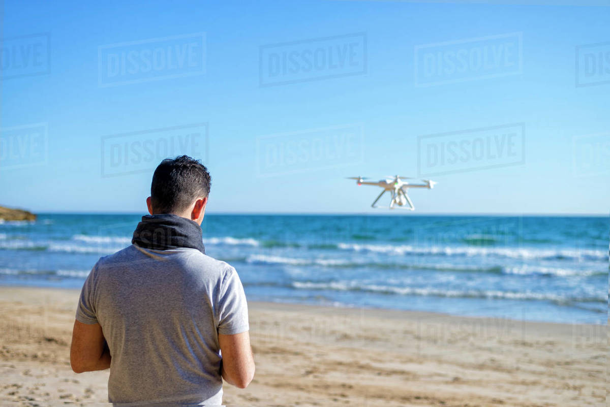 Rear view of a Man on a beach testing its drone and recording v Royalty-free stock photo