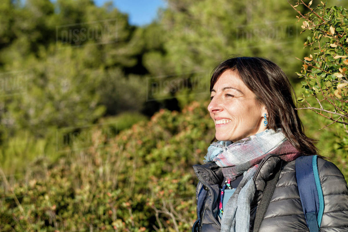 Side view of a smiling woman while standing in the forest Royalty-free stock photo