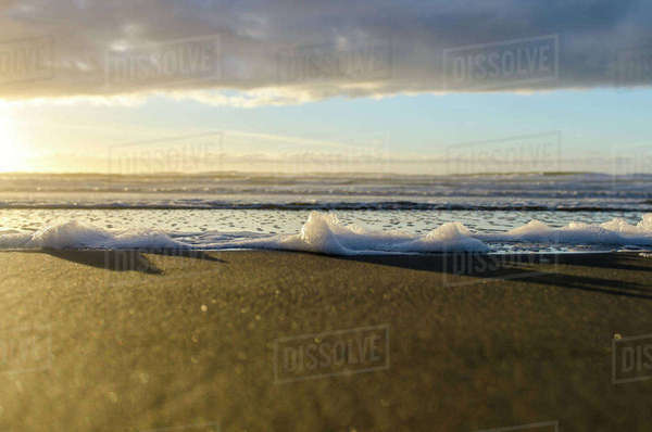 Close-up of sea waves at beach against cloudy sky during sunset Royalty-free stock photo