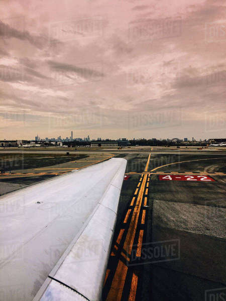 Cropped image of airplane on runway against cloudy sky Royalty-free stock photo
