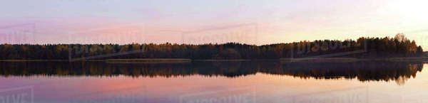 Panoramic view of lake by trees against sky during sunset Royalty-free stock photo