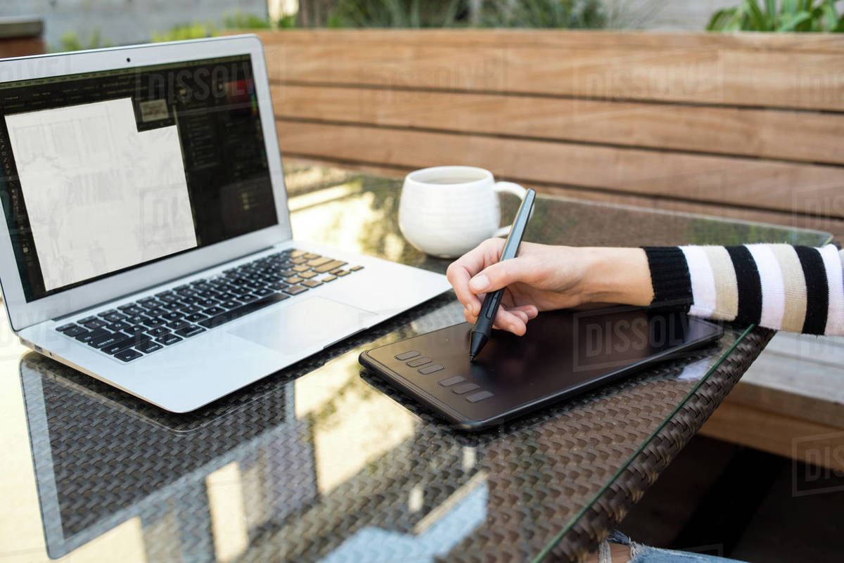 Detail photo of woman using drawing tablet and laptop on outdoor patio Royalty-free stock photo