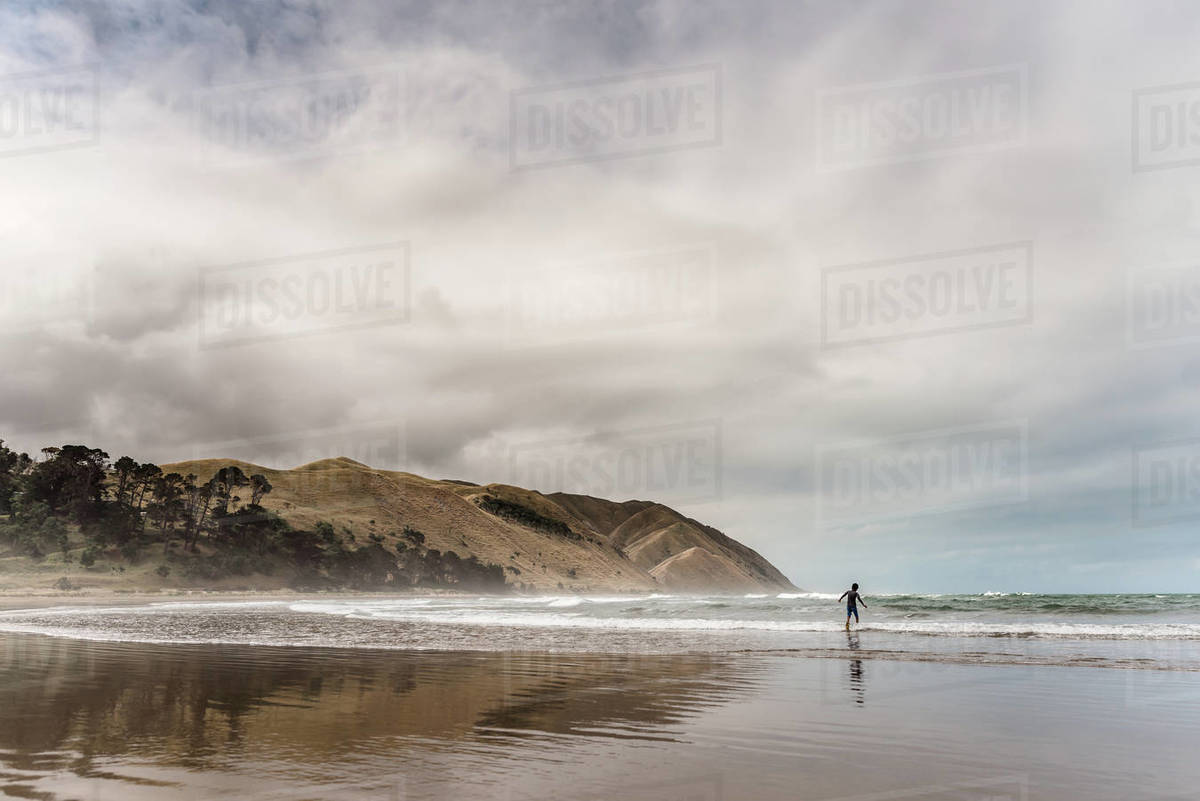 Back view of adolescent boy running into the water at a beach Royalty-free stock photo