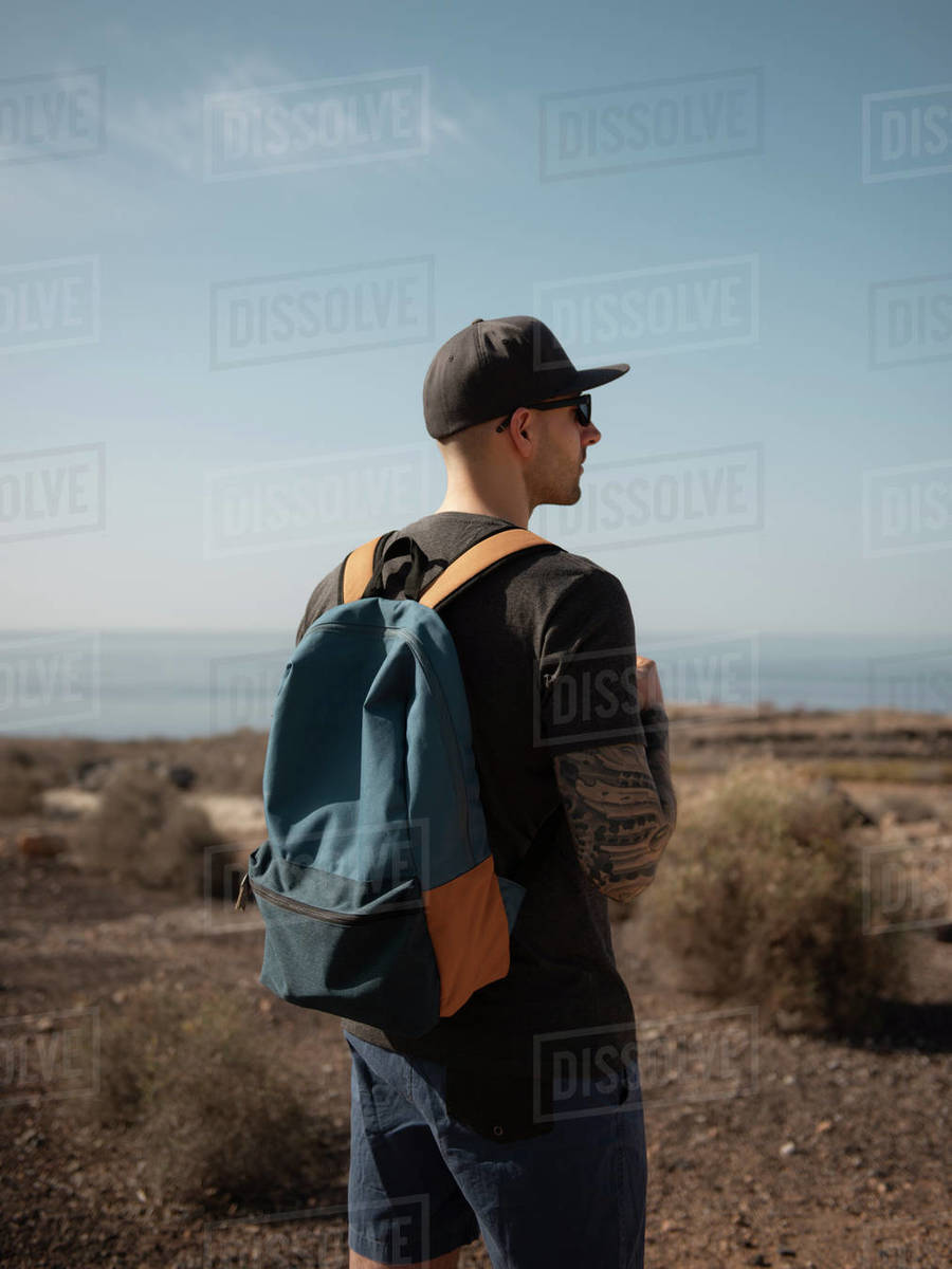 Young Male Traveler Against The Atlantic Ocean Looking Away Sunny Day Royalty-free stock photo
