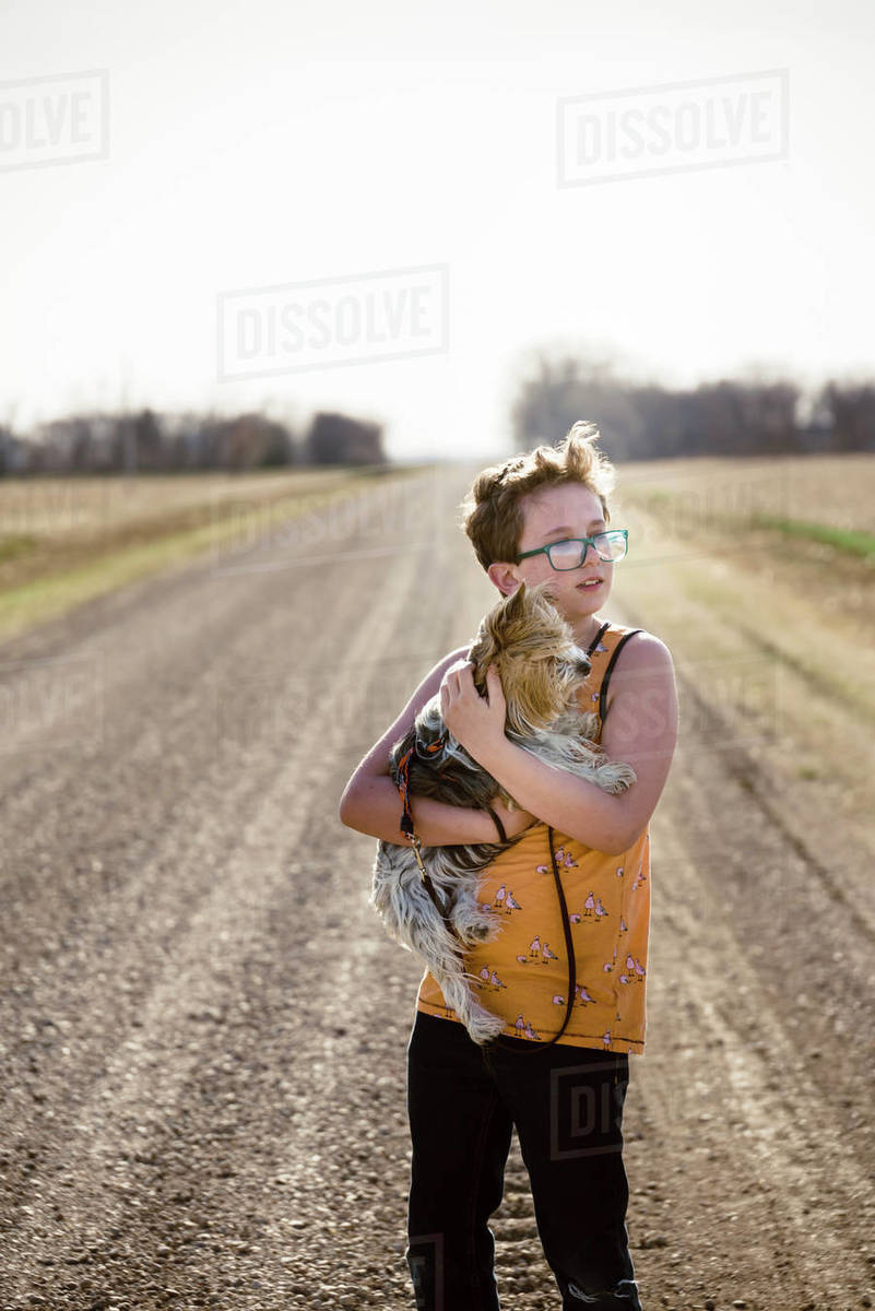 Tween Boy holding his pet looking across a field outdoors on a road. Royalty-free stock photo