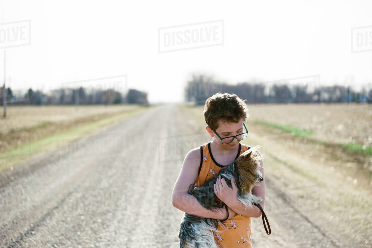 Backlit picture of a boy with his pet Yorkie outdoors. Royalty-free stock photo