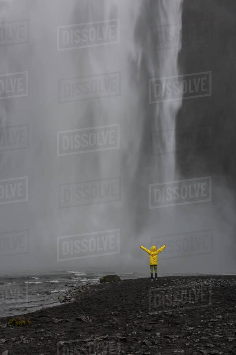 Person with arms raised in front of waterfall, Skogafoss Royalty-free stock photo
