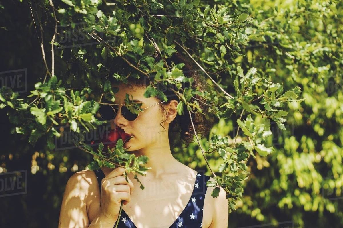 Pretty young girl with sunglasses and red rose among branches Royalty-free stock photo