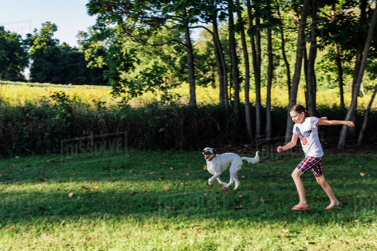Young Girl Running in a Yard with her English Setter Royalty-free stock photo