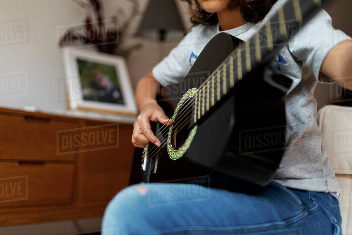 Mid section Boy playing guitar in the livingroom Royalty-free stock photo