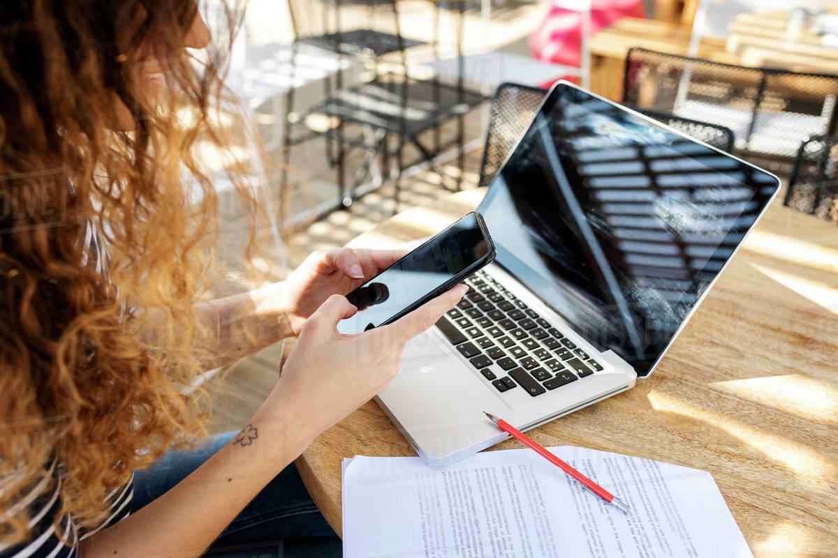 Mid section of a woman texting while working in a terrace Royalty-free stock photo