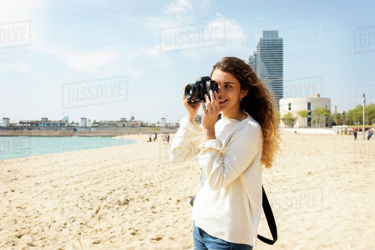 Smiling young woman taking pictures in Barcelona beach Royalty-free stock photo