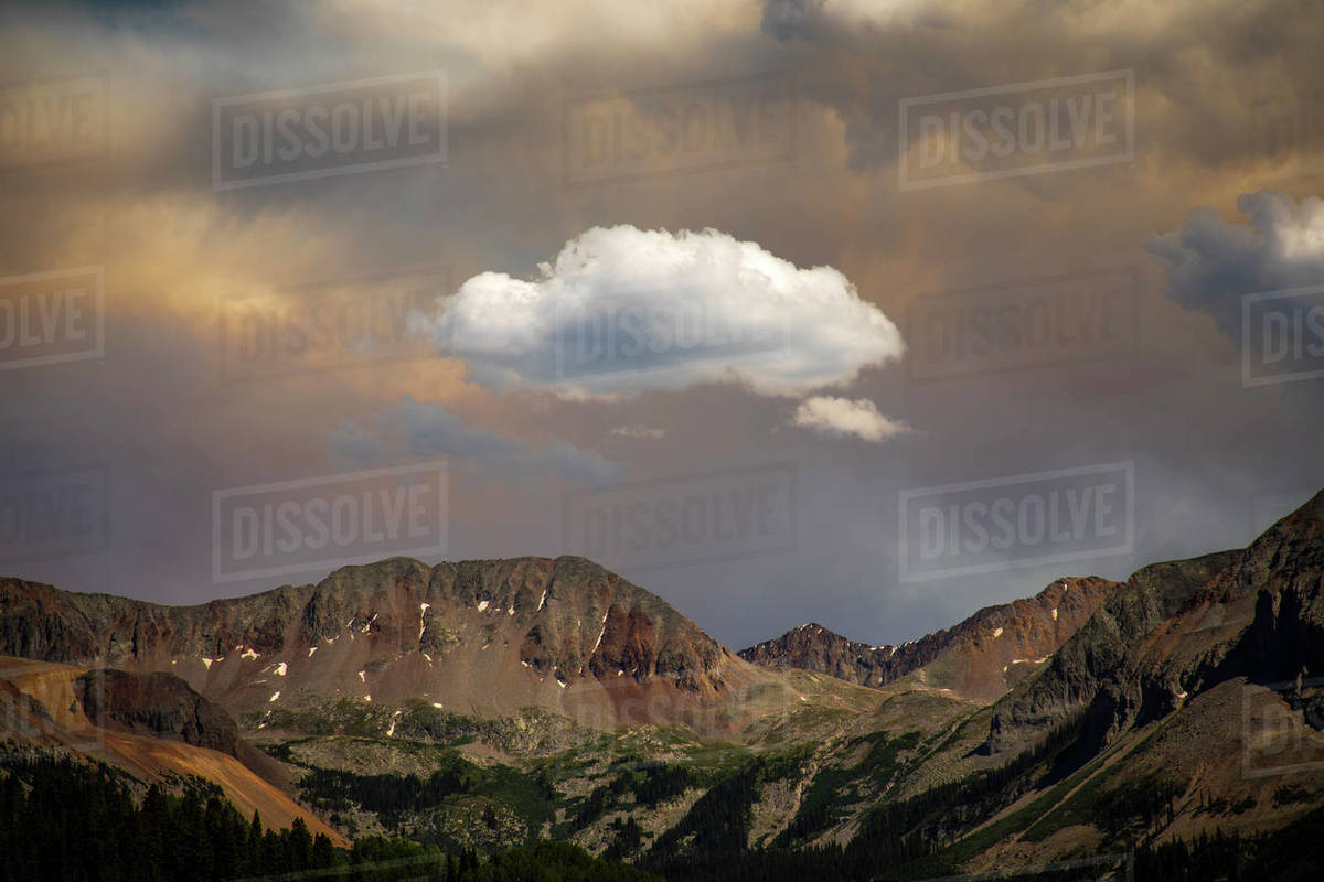 A single cloud stands out from the background of mountains and clouds. Royalty-free stock photo