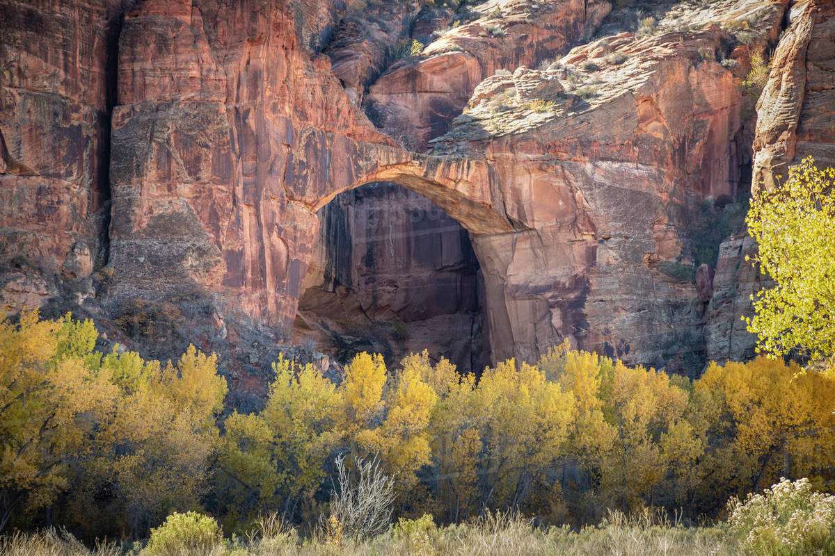 Natural sandstone arch in a canyon in the outdoors during fall colors. Royalty-free stock photo