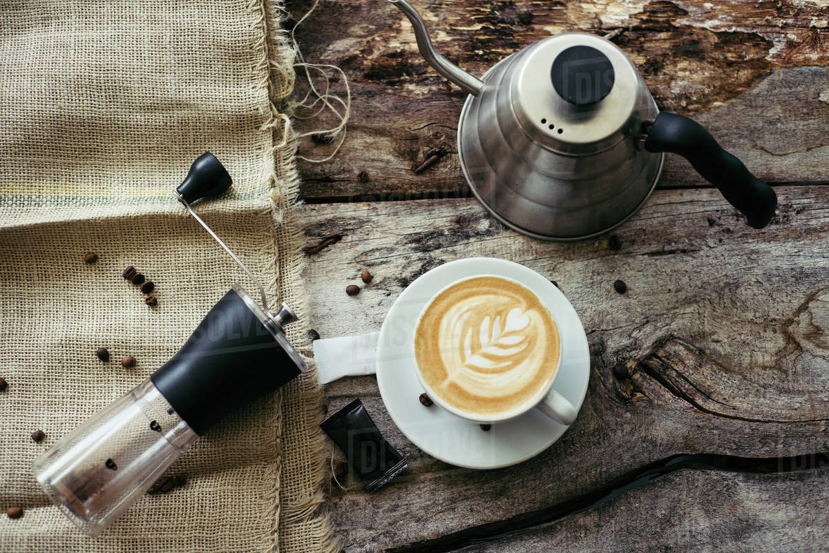 Manual grinder, kettle and creative coffee on the old table. Royalty-free stock photo