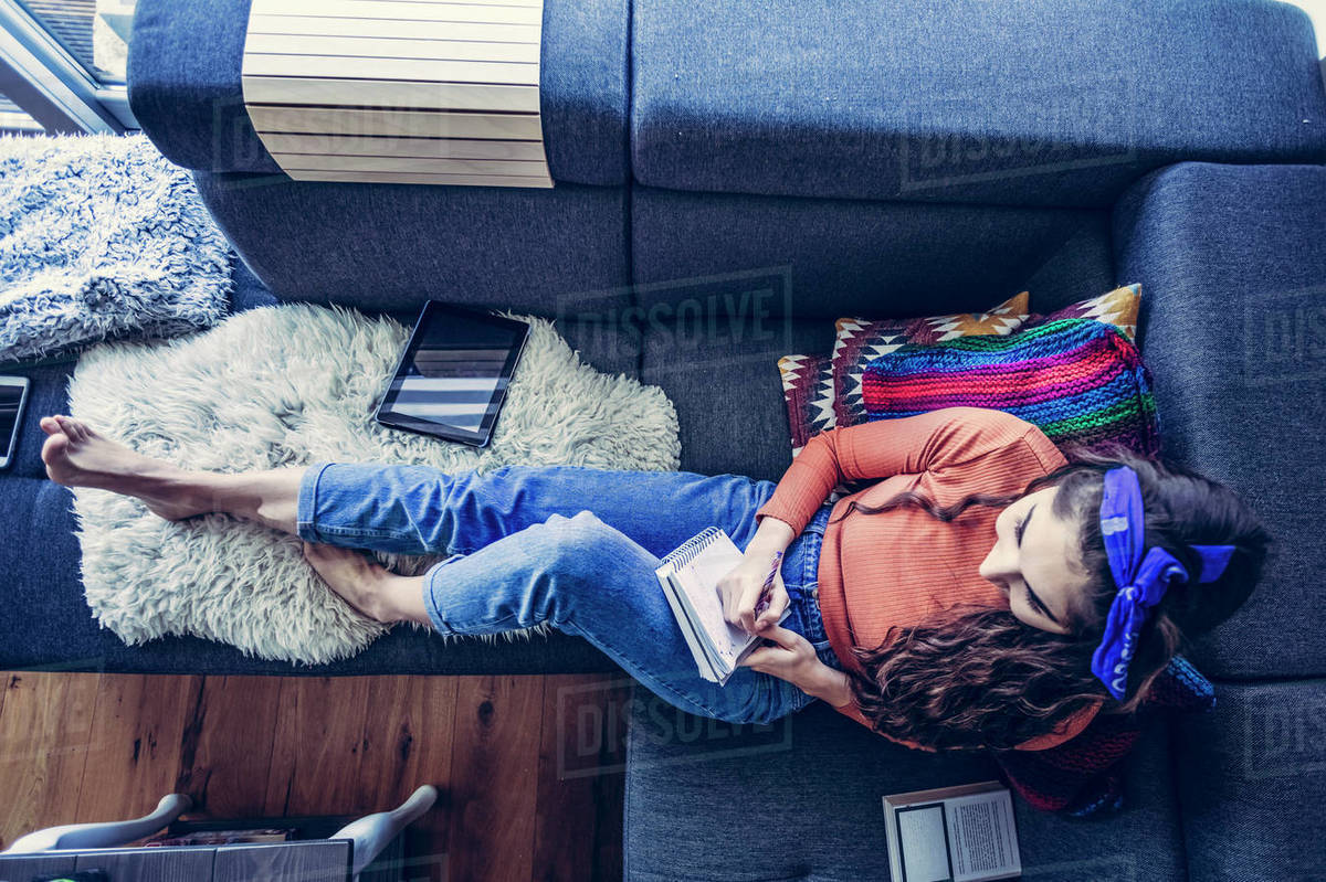 Top view of young woman sitting on couch and writting in notebook Royalty-free stock photo