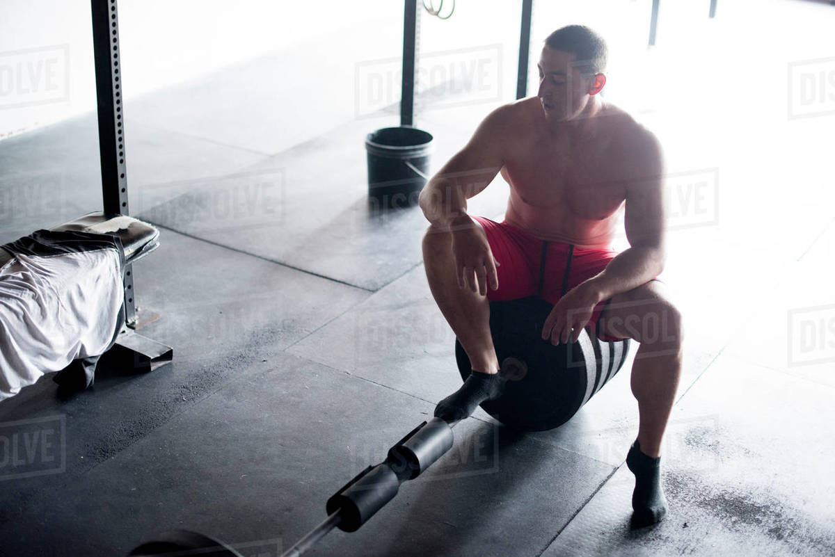 A weightlifter rests on a barbell after deadlifting. Royalty-free stock photo