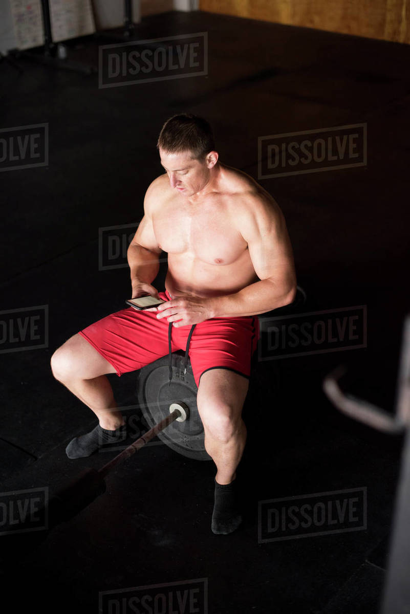 An athlete takes notes on his phone after a workout. Royalty-free stock photo