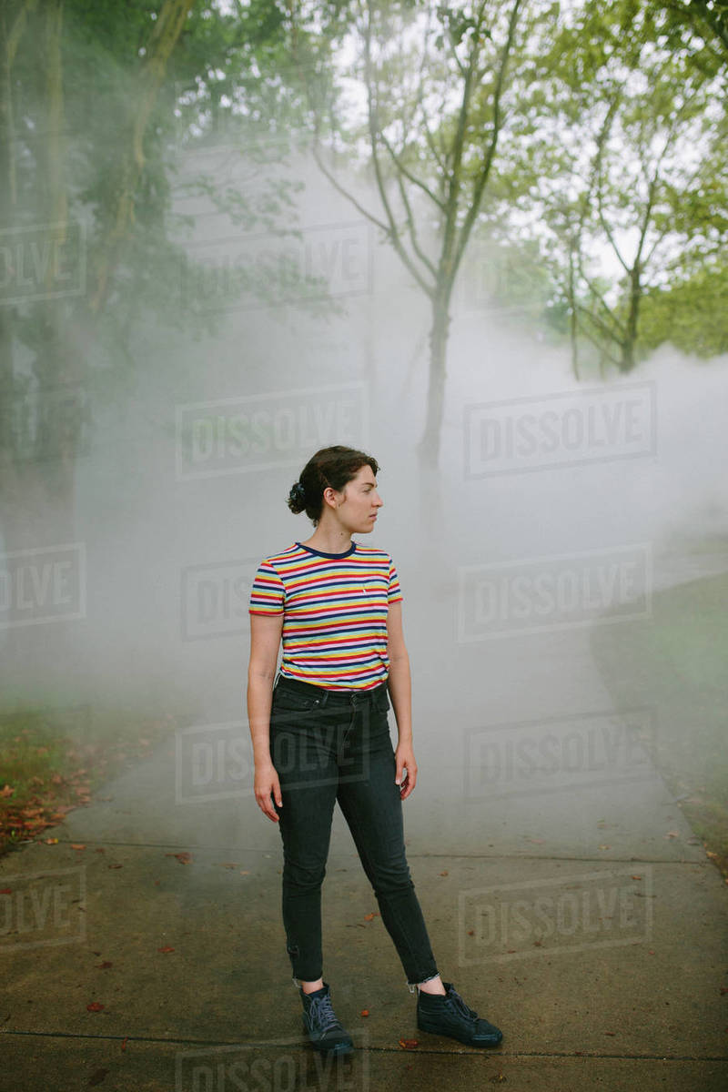 Young woman standing on a foggy path in a park looking away Royalty-free stock photo