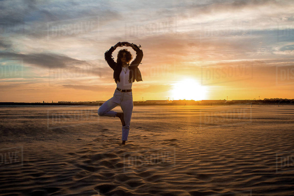 Woman on the beach at sunset doing yoga Royalty-free stock photo