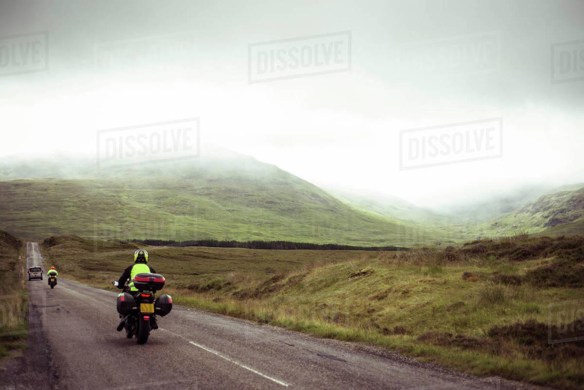 Motorbikes travel wet road through misty mountains in Scotland Royalty-free stock photo