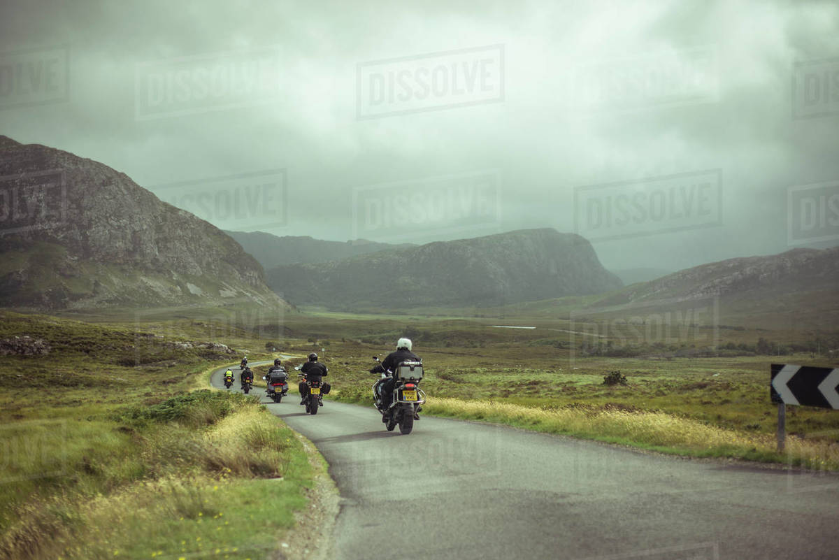 Line of motorbikes ride on small winding road through remote mountians Royalty-free stock photo