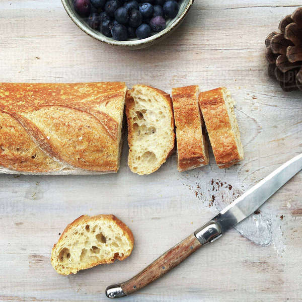 Overhead view of bread with knife by blueberries and pine cone on table Royalty-free stock photo
