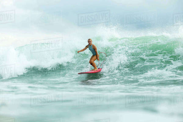 Woman surfing in sea against cloudy sky Royalty-free stock photo