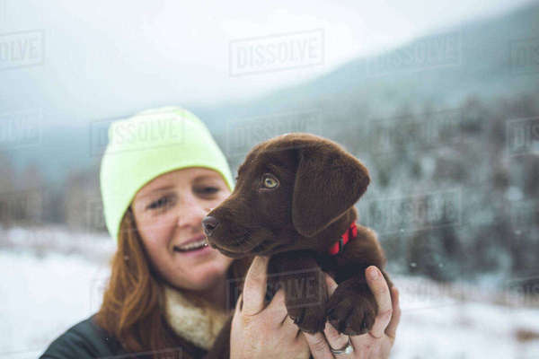 Happy woman with Chocolate Labrador standing on field during winter Royalty-free stock photo