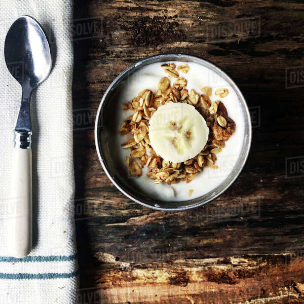Overhead view of food in bowl with spoon and napkin on wooden table Royalty-free stock photo