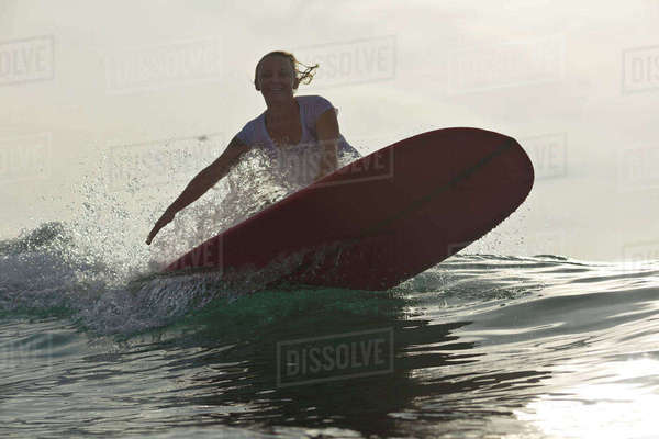 Portrait of happy woman surfing in sea against sky Royalty-free stock photo