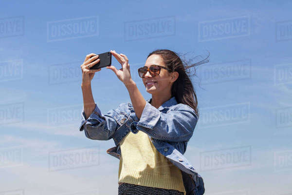 Low angle view of beautiful woman photographing through smart phone against sky Royalty-free stock photo