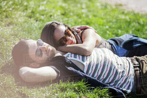 Romantic couple lying on grass during summer Royalty-free stock photo