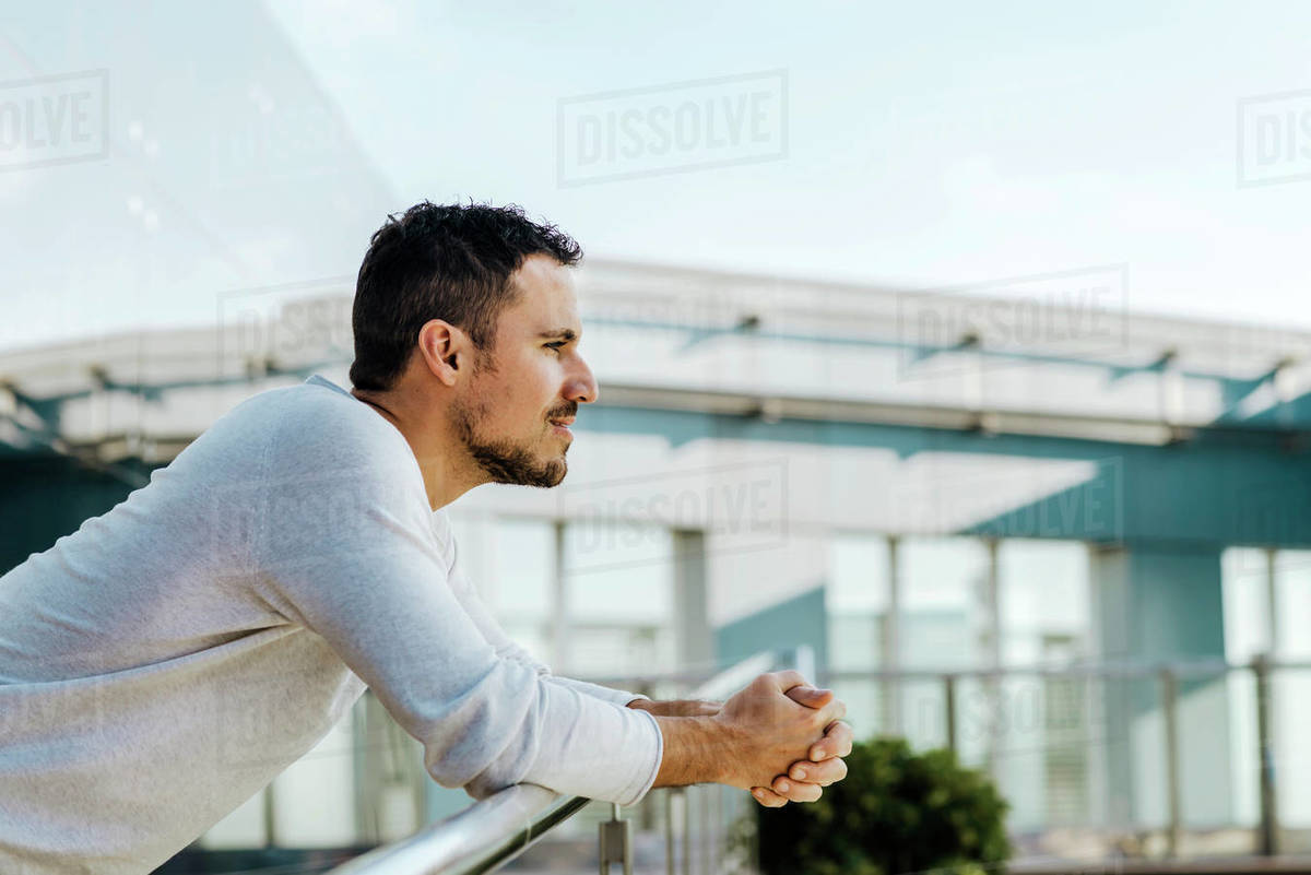 Man leaning on railing of footbridge looking at distance Royalty-free stock photo