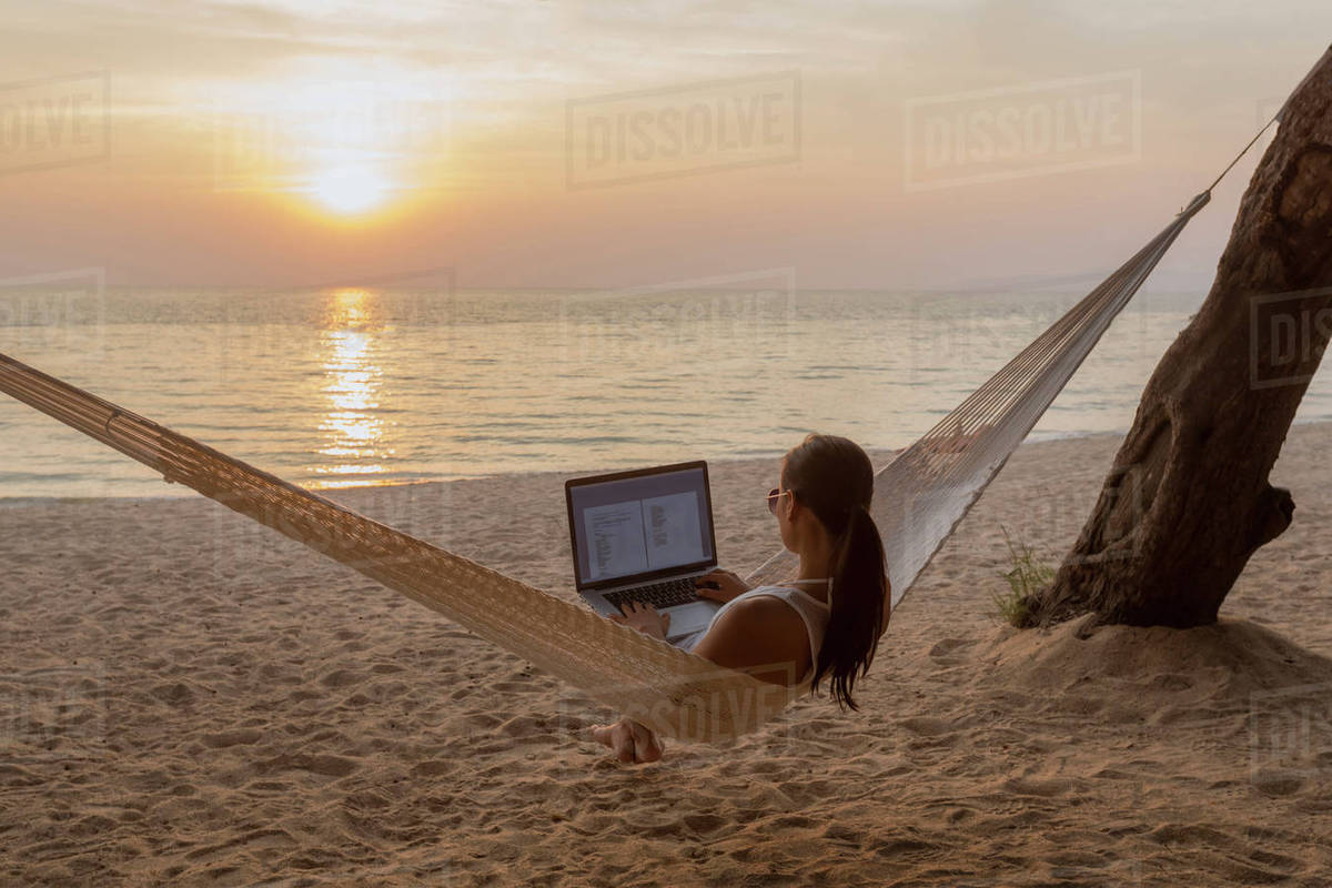 f203878b21957 Woman using laptop computer while sitting on hammock at beach ...