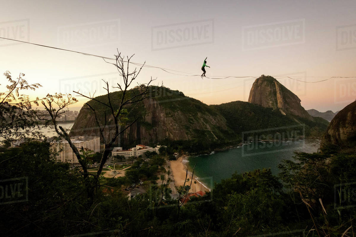 Slackliner walking on highline on beautiful sunset near Sugar Loaf Royalty-free stock photo