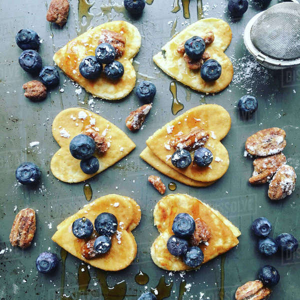 High angle view of heart shaped pancakes with blueberries and pistachios on table Royalty-free stock photo