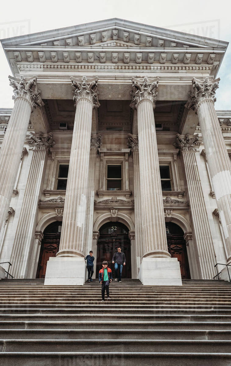 Man and two boys walking down steps of historic building in NYC. Royalty-free stock photo