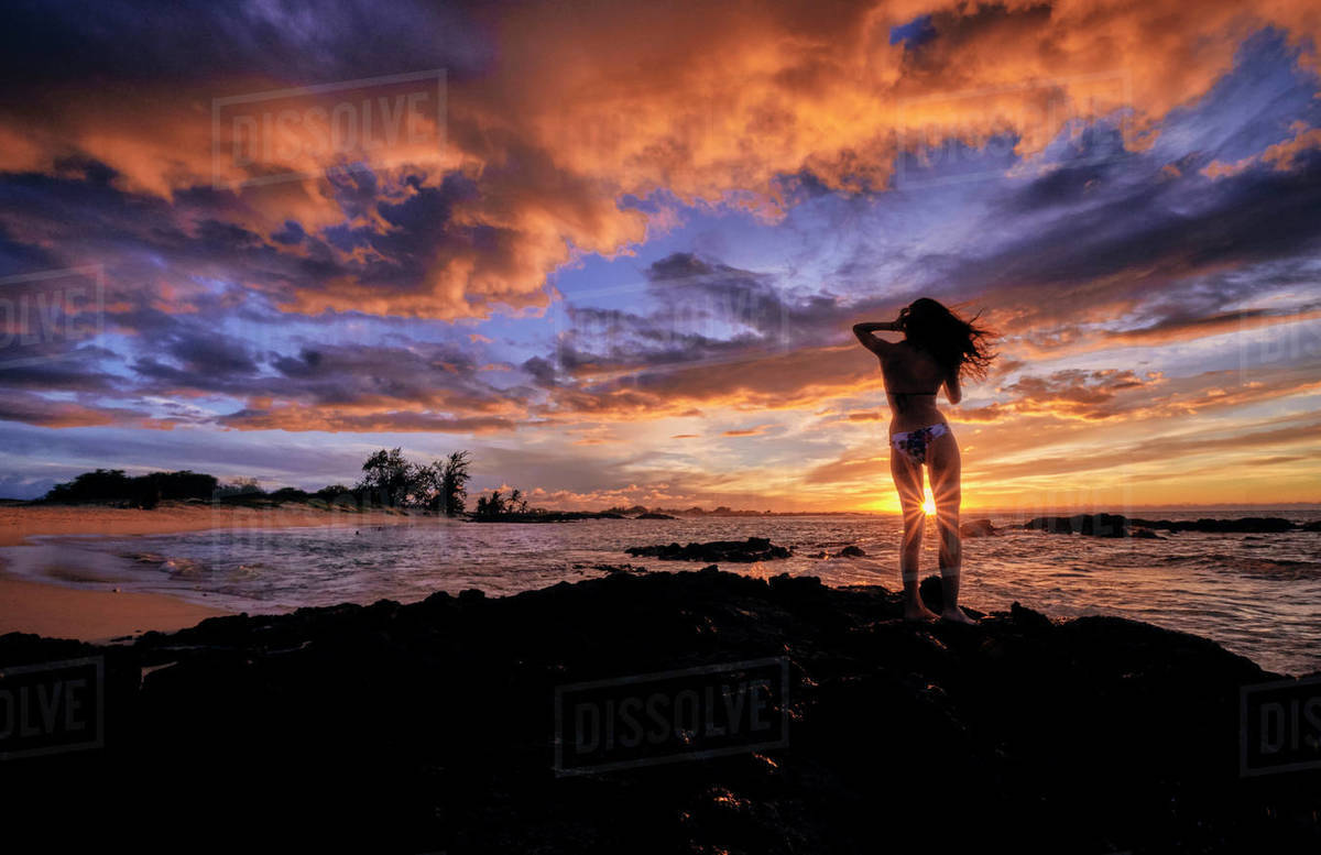 A young woman stops to celebrate the sunset on Makalawena Beach Hawaii Royalty-free stock photo