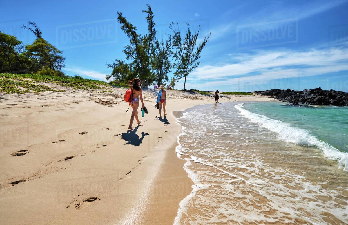Three friends walk along the ocean toward Makalawena Beach, Hawaii Royalty-free stock photo