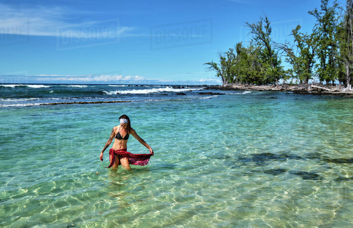 A young woman walks out of a shallow lagoon near Makalawena Beach Royalty-free stock photo